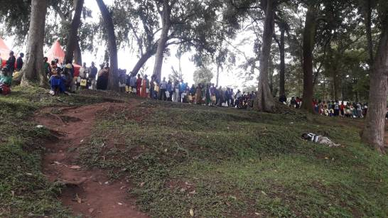 People in line to get their water from the stream.