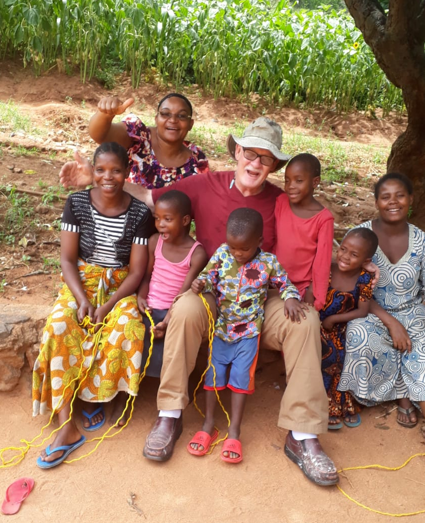 Pete is wearing a big smile, sitting on a curb and surrounded by seven smiling children, some holding jump ropes.